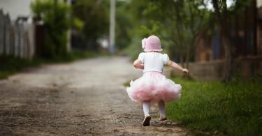 little girl in dress running away