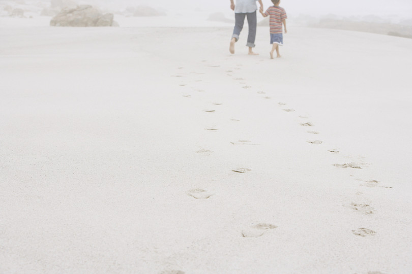 Rear view of father and son walking leaving behind footprints on