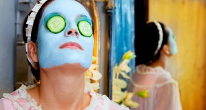 Funny housewife beauty green clay mask and cucumber at the mirro