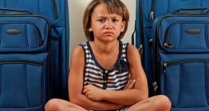 A young girl sits in front of suitcases with a sad expression on her face.