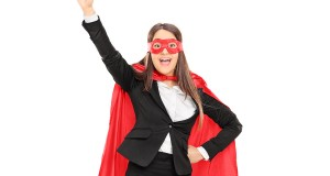 Woman in superhero costume with raised fist isolated on white ba