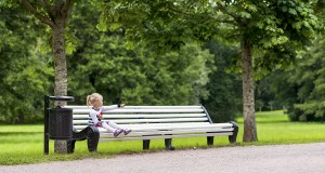 Little Blonde Girl Sitting On The Bench In The Park