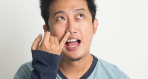 Disgusting Asian man picking nose with eyes looking up, on plain