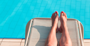 Unrecognizable Woman Tanning Near Swimming Pool