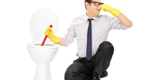 Young man unclogging a stinky toilet with plunger isolated on wh