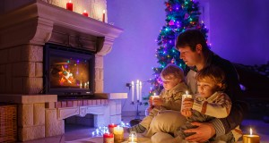 Young Father And His Little Children Sitting By A Fireplace On C