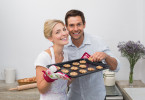 Portrait of happy young couple with freshly baked cookies in the