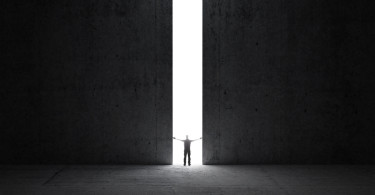 Dark Abstract Concrete Interior. Man Stands In The Light Of Open
