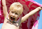 Excited Child In Beach Towel On Summer Day
