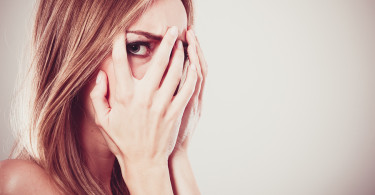 Afraid frightened woman peeking through her fingers on grey. Shy teen girl covering face with hands.