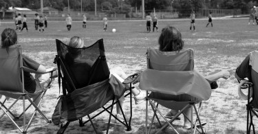 Soccer moms watching young team play on field