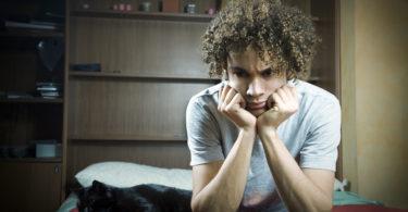Young Brazilian teenager sad and upset in bedroom