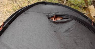 Young woman looks out of tent