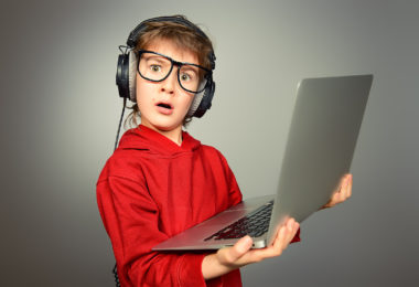 Cute boy in spectacles and headphones holds his computer. He is