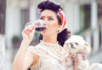 Youngwoman with little puppy, drinking red wine