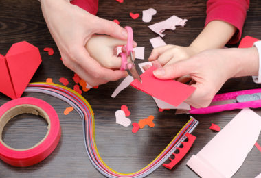 hands cutting paper for Pinterest Valentine's crafts