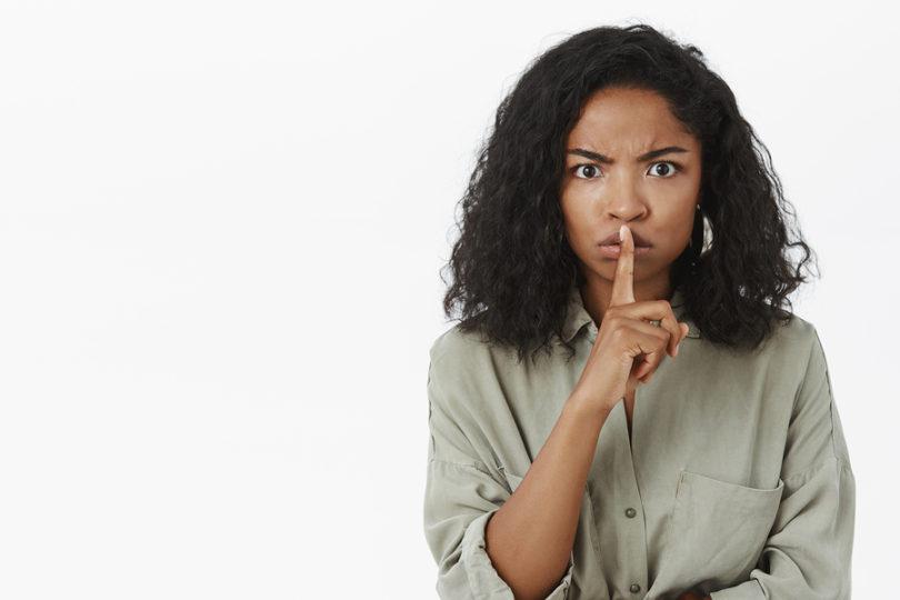 Woman signaling shut up.