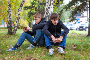 teenage boys sitting under tree
